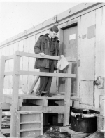 Brown examining waste discharge bucket at barracks entrance